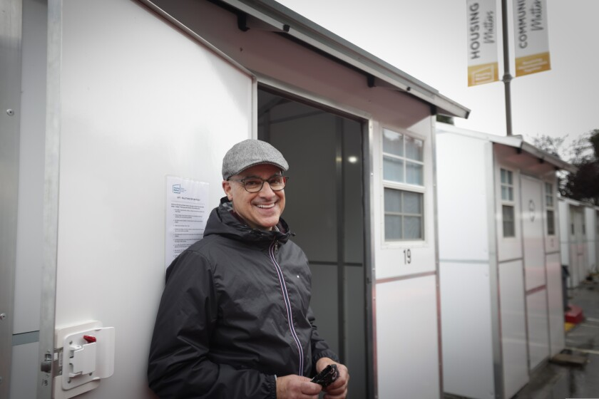 Housing Matters Executive Director Phil Kramer stands by a Pallet shelter.