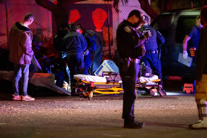 A victim of a stabbing is given medical attention by EMS at the scene of a double-stabbing on Front Street.