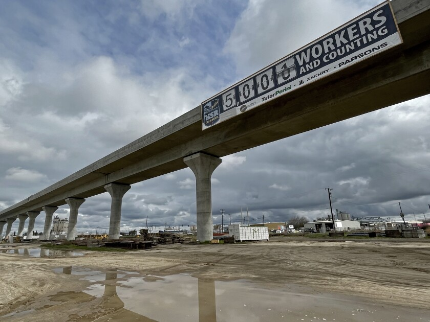 California rail authority banner claims 5,000 workers on the project on a viaduct in Fresno.