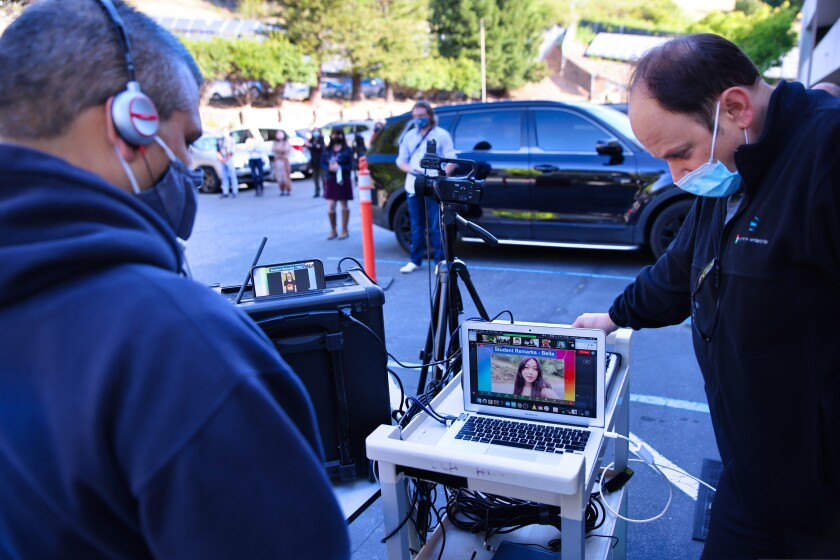 County office of education staff help run the virtual flag-raising ceremony from the office's parking lot on Tuesday.