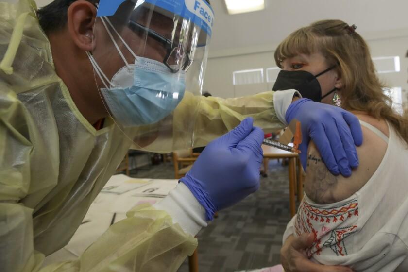 Bryan Phan, a RN, left, administers a Johnson & Johnson COVID-19 vaccine to Linda Davis, 60