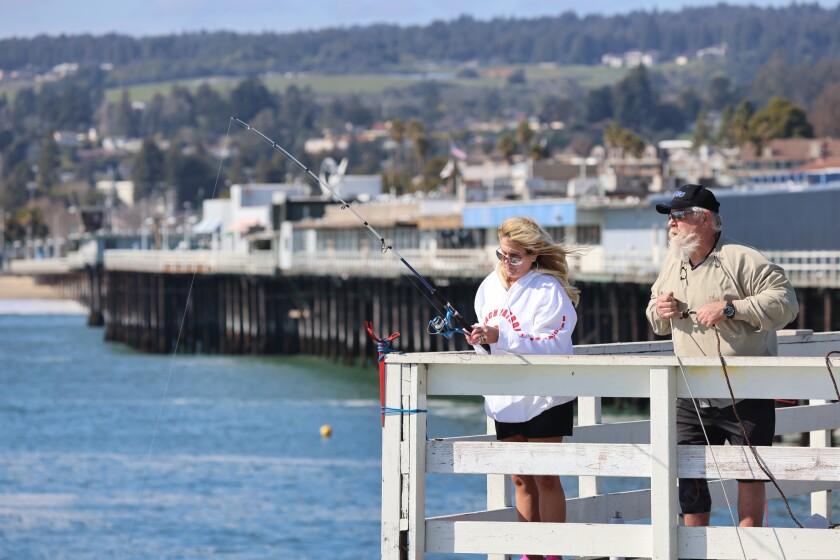 Dawn Kole and Sean Crawford of Ripon fish at the Santa Cruz wharf on March 8, 2021.