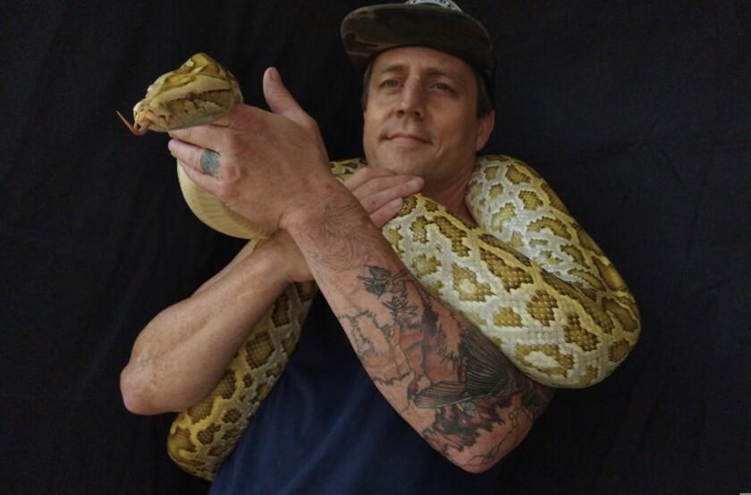 A man holds a large snake