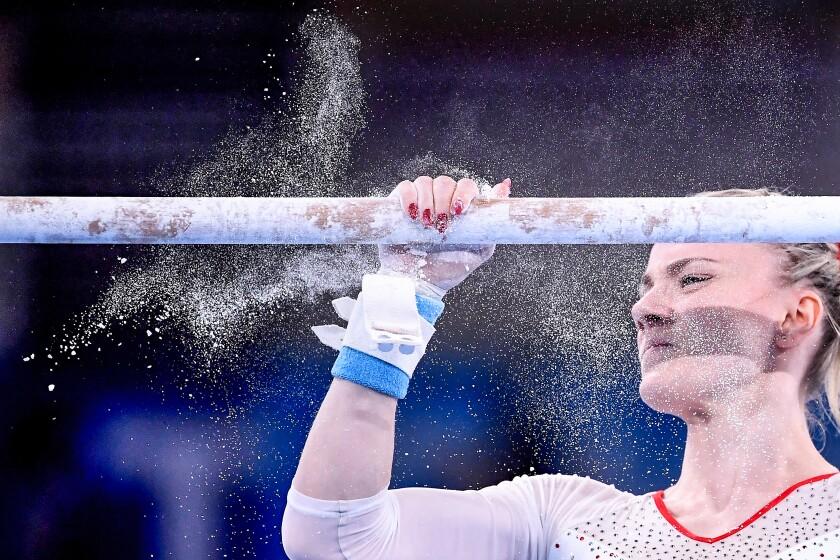 Powder flies as Poland's Gabriela Sansal prepares to compete on the uneven bars