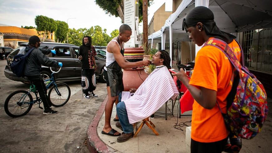 Jacket Rashad, a street barber, gives Rashad Karim, a food vendor, a haircut on Degnan Blvd.
