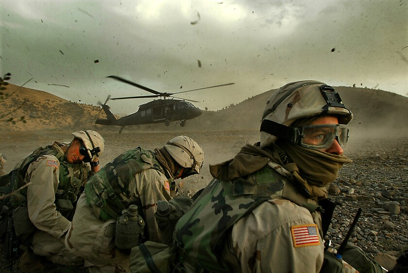 Members of the 82nd Airborne duck away from the debris as a helicopter lifts off in Afghanistan