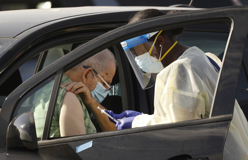 Staff and volunteers distribute the COVID-19 vaccine to people as they remain in their vehicles at The Forum in Inglewood