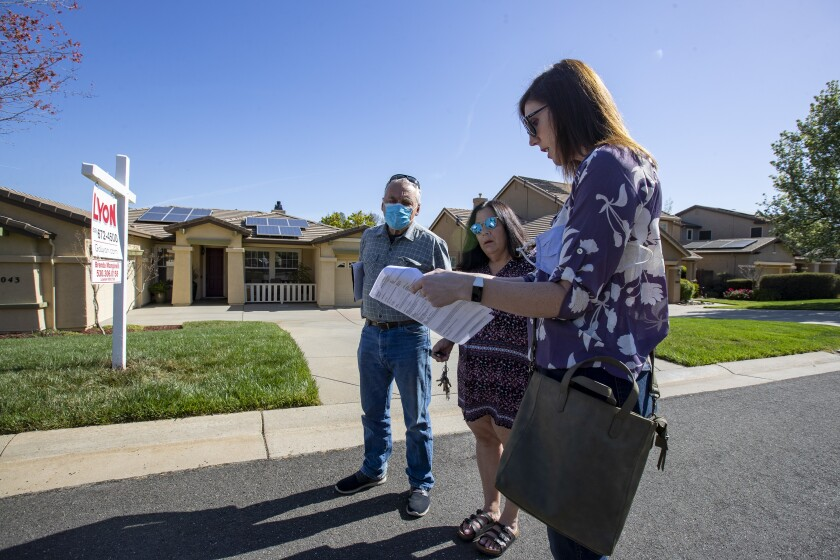 Real estate agent Morgan Larson, right, prepares to show a home to prospective buyers Gary and Karen Edmondson.