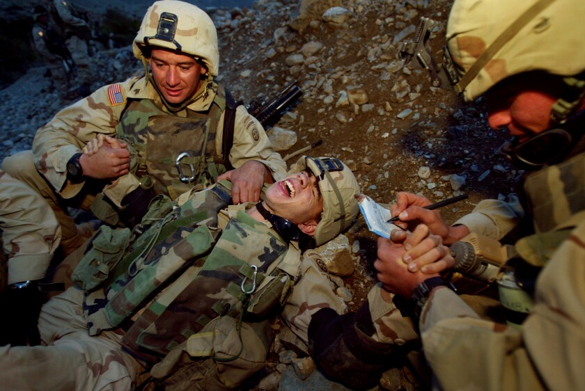 A soldier lies on the ground yelling as other soldiers tend to him