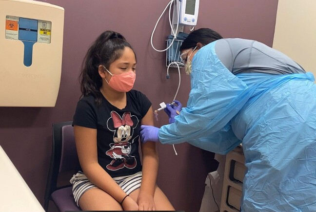 Luci Guardino, 11, receives her first dose of a COVID-19 vaccine