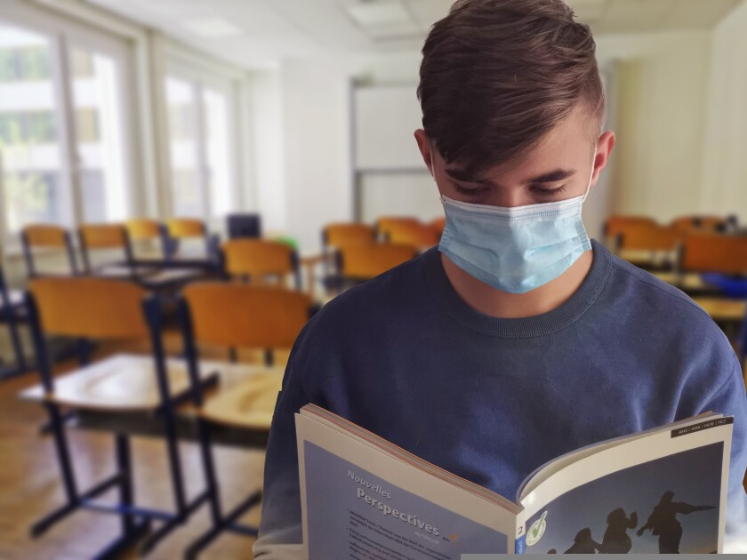 A masked student reads a book in an empty classroom