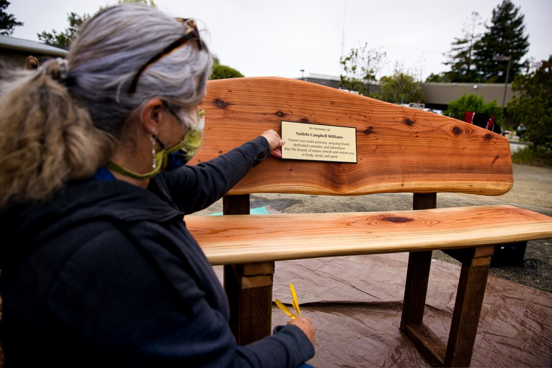 Sherry Lee Bryan shows off the redwood bench with plaque for Vai.