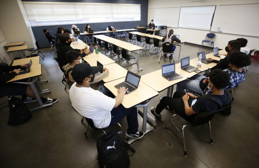 Masked students, many in close proximity, sit at desks arranged in a U shape