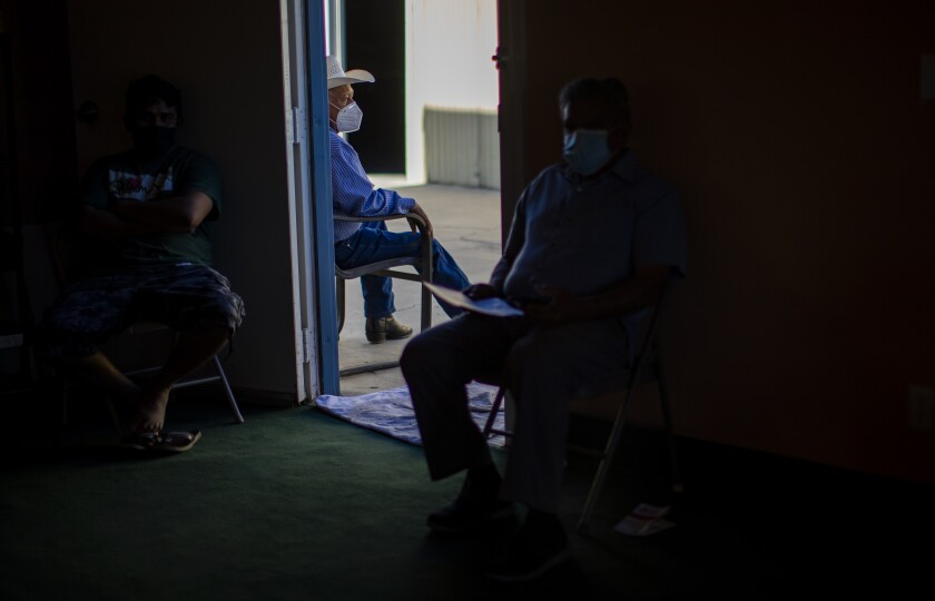 Farmworkers wait to get a COVID-19 vaccine.