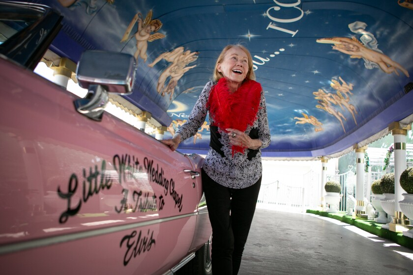 Charolette Richards, owner of the Little White Chapel, poses next to the pink Cadillac in the Tunnel of Love