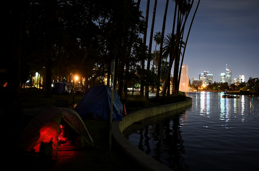 A glow is visible inside a tent along a lake after dark, with the city skyline in the background.