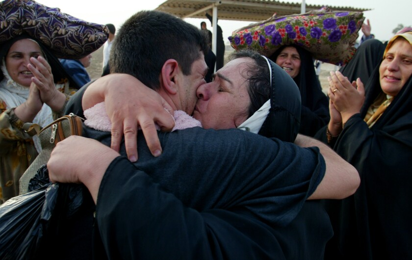 A man hugs his mother as other people around them clap