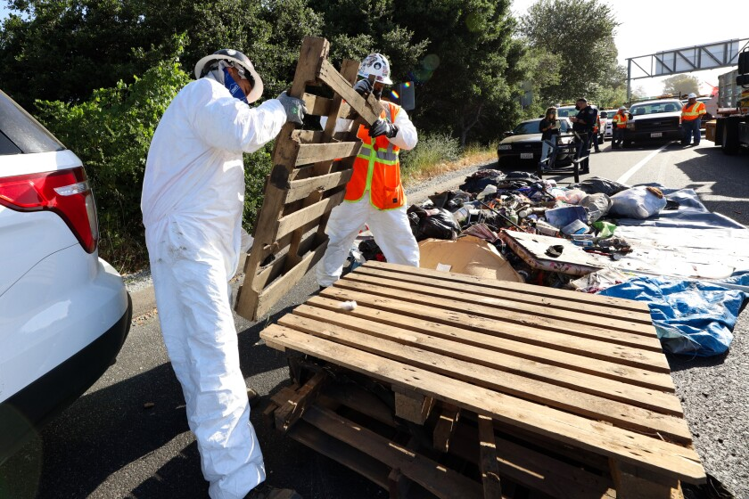 Caltrans cleanup crews begin the process of clearing out the Highway 1/9 camp amid evictions on Monday morning.