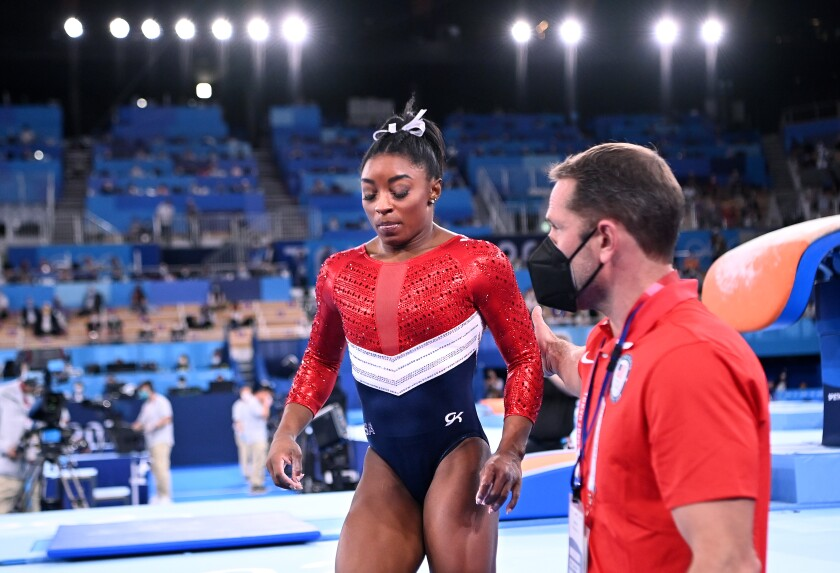 Simone Biles leaves the floor after competing on the vault during the women's team gymnastics