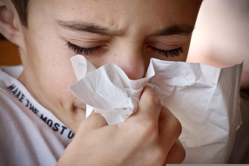 A boy sneezes