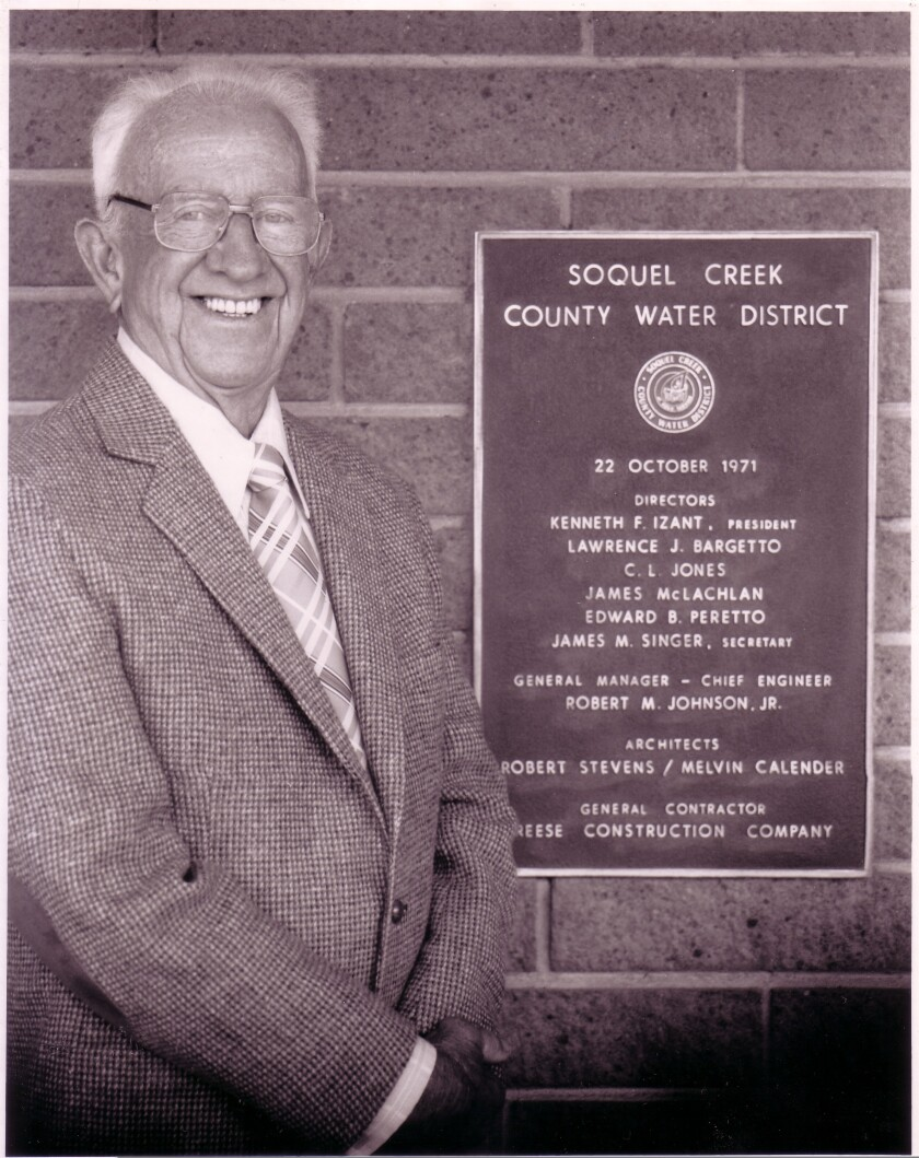 Ken Izant standing with the original District plaque at the District office. Ken was the Board President from 1961-1983.