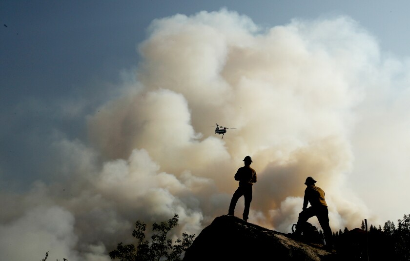 Firefighters watch a helicopter battle the Dixie fire as it burns through mountainous and forested terrain