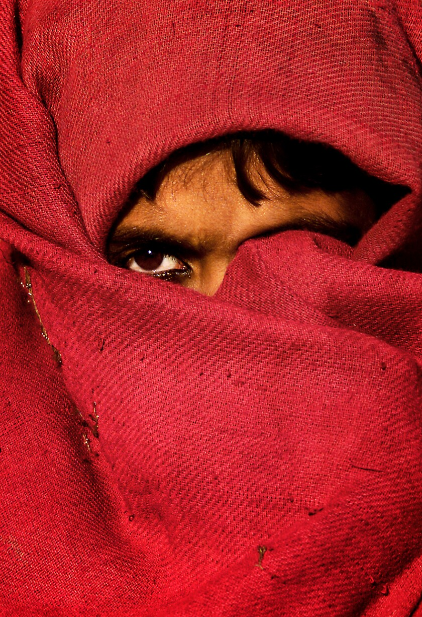 A girl with her face mostly covered by red cloth