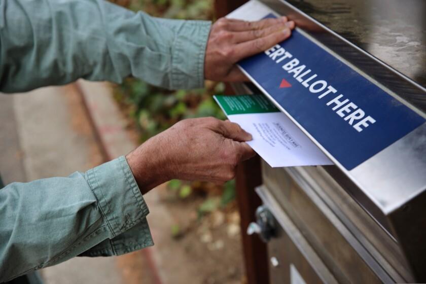 A voter drops a ballot in a drop box