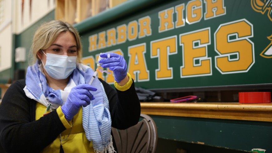 A COVID-19 vaccination being prepared at Harbor High School.