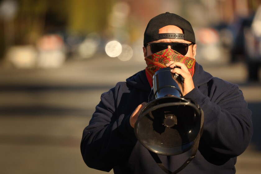 Carlos Cruz speaks through a megaphone at a rally outside the home of UCSC Chancellor Cynthia Larive this month.