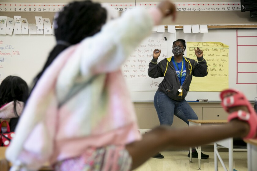 """Kindergarten teacher Ms. Copes encourages students to dance to Kool & The Gang's """"Celebration"""" during summer classes for rising first graders at Laurel Elementary in Oakland on June 11, 2021. Photo by Anne Wernikoff, CalMatters"""