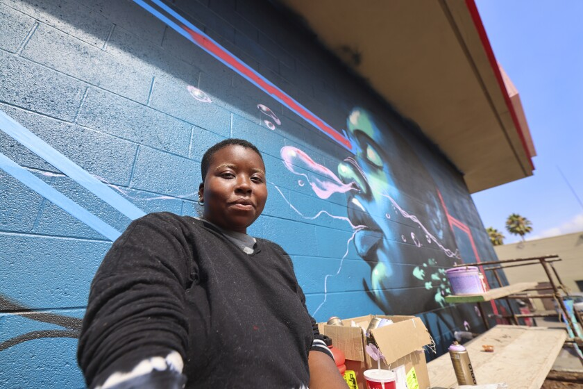 """Oakland artist Zoe Boston with her """"Species at Risk"""" mural at 1827 Soquel Ave. on Friday."""