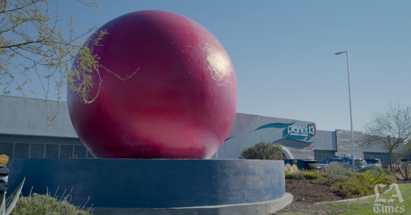 A large red globe that's also a water element with a building in the background.