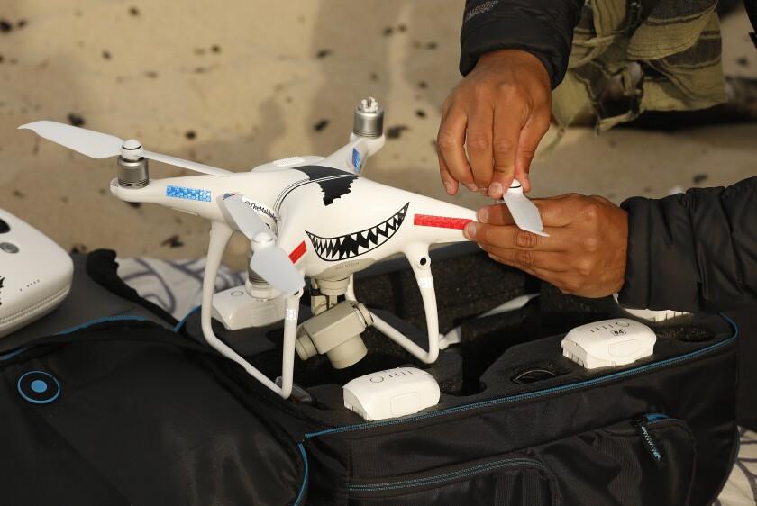 Carlos Gauna prepares a drone for launch