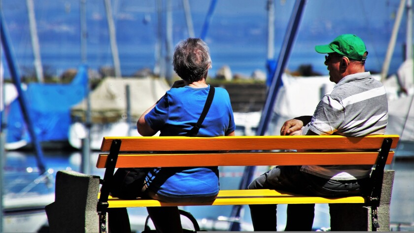 Two older adults sit on a bench near water