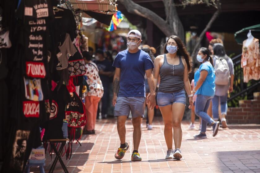 Wearing face masks Manuel Jaimes, 21, left, and Liliana Lomeli, 21, right, both of Stockton, walk through Olvera Street