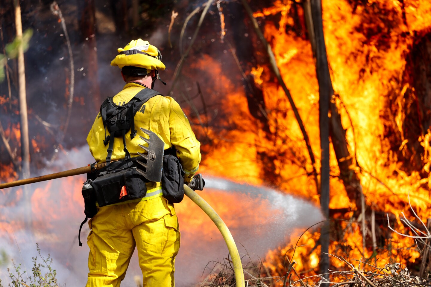 Firefighters from Aptos fire work to put out a blaze off of Gillette Rd. in Watsonville