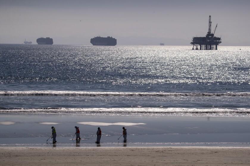 A crew cleans up oil chucks Tuesday from a major oil spill in Huntington Beach.