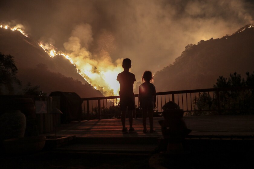 Iris, 4, and Castle Snider, 8, look on as flames engulf the hillsides behind their backyard as the Bobcat Fire burns.