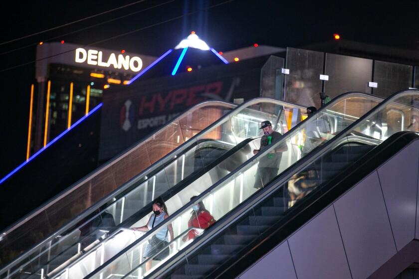 A few people in masks ride down an escalator on the Las Vegas Strip