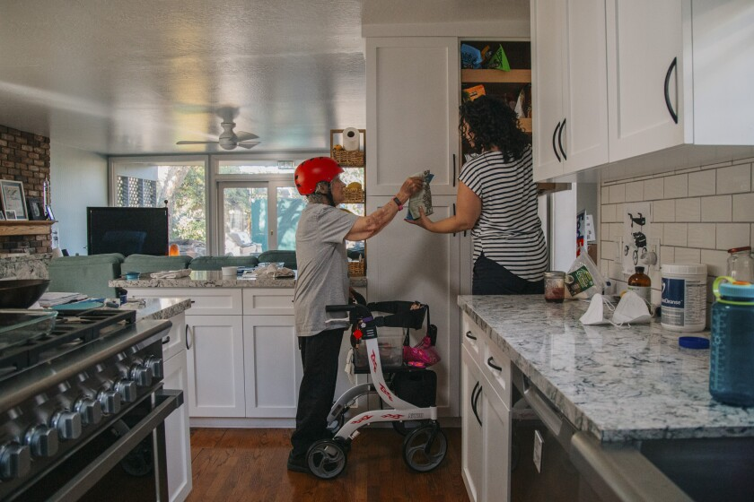 Ann Lucero helps her mother, Fern, gather ingredients to make homemade granola at their home in Redwood City on Oct. 11, 2020. Photo by Clara Mokri