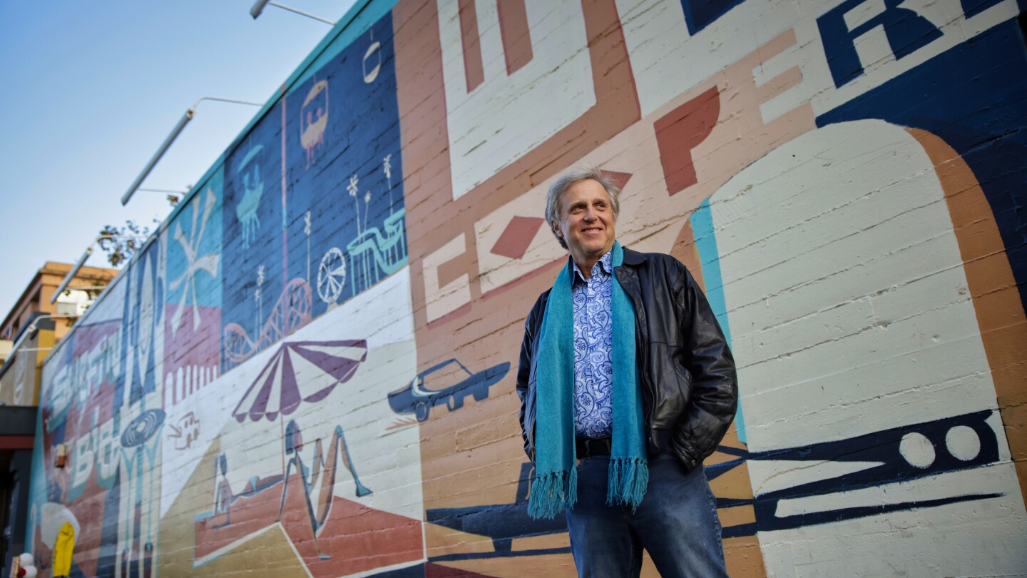 Wallace Baine in front of a Santa Cruz mural