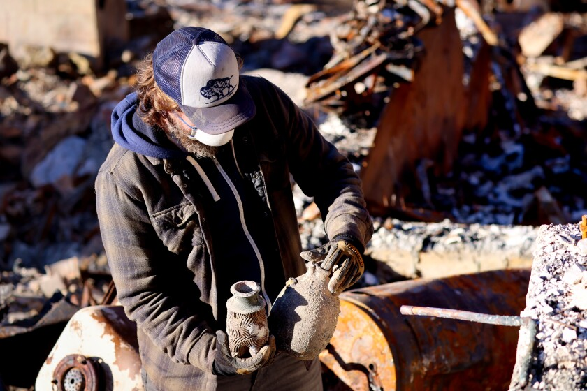 Jon Payne sorts through the wreckage, salvaging a few keepsakes.