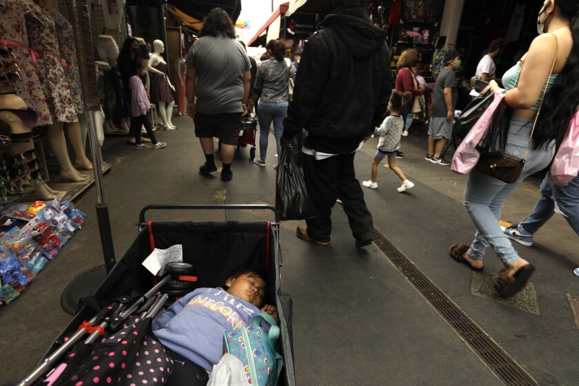 Malia Soto sleeps in a wagon while her parents shop at Santee Alley in downtown L.A.